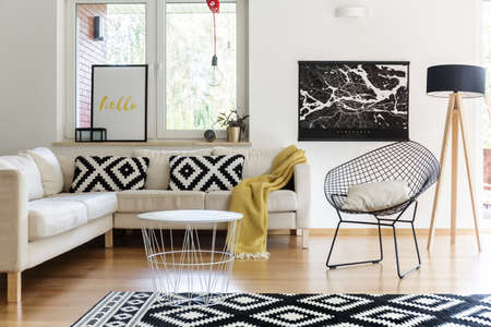 Bright living room interior design with white table, corner sofa and black poster 写真素材