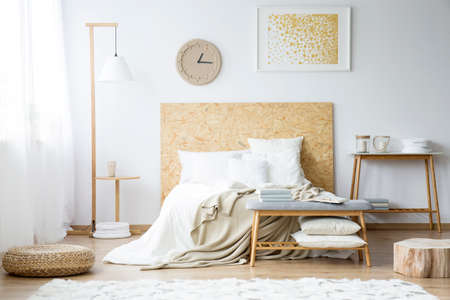 Paper clock and gold painting on the wall above bed with beige bedsheets in bedroom with pouf and wooden furniture