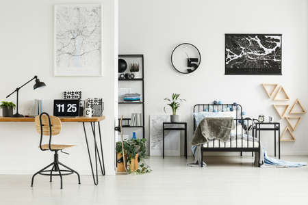 Study corner with lamp, laptop, and notebooks on hairpin table in white bedroom with posters