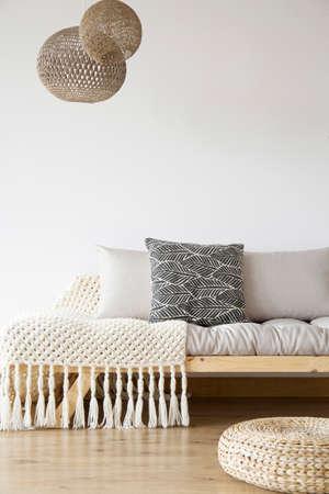 Gemusterte Decke auf hölzernem Bett, Pouf und Lampen im hellen Schlafzimmer mit Kopienraum auf weißer Wand