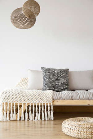 Patterned blanket on wooden bed, pouf and lamps in bright bedroom with copy space on white wall