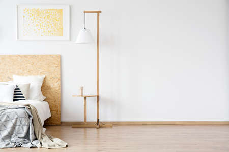 Wooden lamp next to bed with patterned bedding in warm bedroom with gold painting on the wall with copy space Standard-Bild