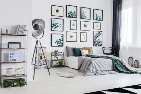 Green suitcase lying under black metal rack with books, candle and decorations in white bedroom