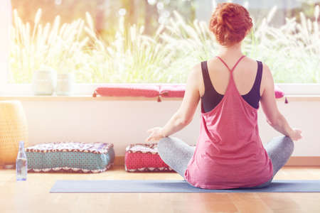 Young woman sitting cross-legged on a sports mat during yoga classes at a peaceful gym Stock Photo