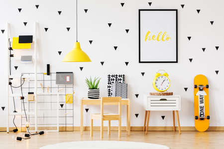 Poster above white cabinet with yellow clock between skateboard and wooden desk in cozy kindergarten interior