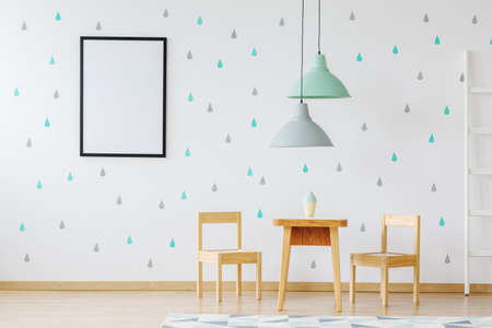 Mockup of poster on wallpaper in childs room with wooden furniture and grey and mint lamps