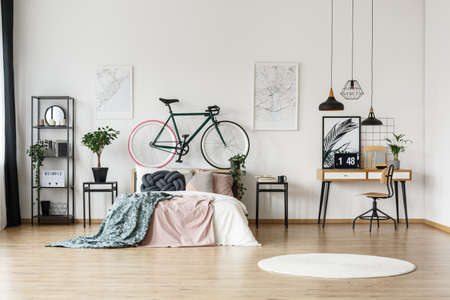 White round rug on the floor in bright bedroom with hipster bike and wooden desk Stock Photo