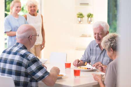 Gente senior che mangia cena mentre sedendosi ad una tavola in casa di cura Archivio Fotografico - 91905601