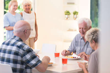 Senior people eating dinner while sitting at a table in nursing house Stock Photo