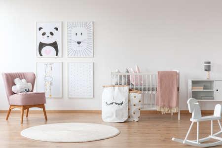 Weißes Schaukelpferd und Teppich im Kinderzimmer mit rosa Lehnsessel, Papiertüten, Zeichnungen und Bett