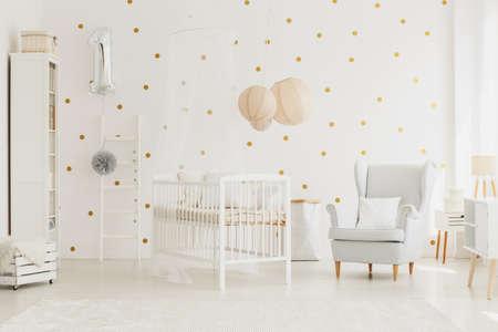 실버 풍선, 회색 안락의 자 및 점선 된 벽 밝은 아기 룸 캐노피와 흰색 나무 침대