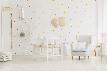 White wooden crib with canopy in bright baby room with silver balloon, grey armchair and dotted wall