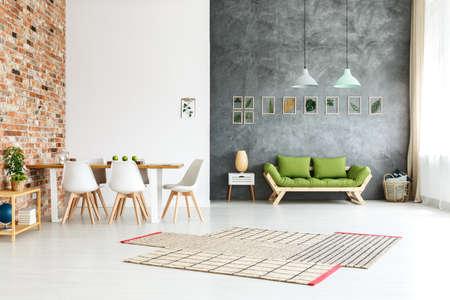 Open vloerhuis met bakstenen muur in eetruimte en houten groene bank tegen donkere geweven muur in heldere woonkamer