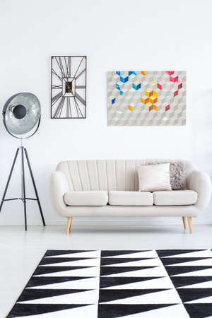 Beige sofa and lamp in bright living room with geometric carpet and poster with clock on the wall