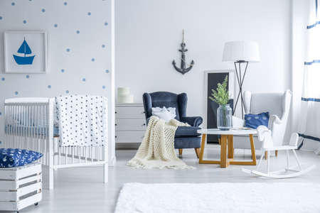 White baby bedroom with painting hanging on the dotted wall and two armchairs by small table