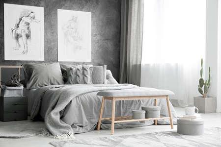 Houten bank en cactus in heldere grijze slaapkamer met bed tegen geweven muur met tekeningen Stockfoto