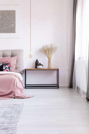 木製ナイト テーブル、アートワークやピンクの寝具で快適な居心地のよいベッドの横にある銅のペンダント電球 写真素材