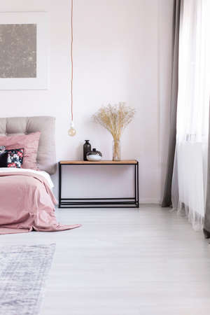 Wooden nightstand, artwork and copper pendant light bulb next to comfortable cozy bed with pink bedclothes