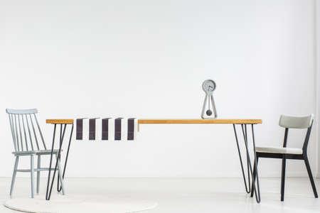 Tavolo in legno con un orologio e un panno a strisce nella sala da pranzo bianca con sedie grigie e spazio di copia