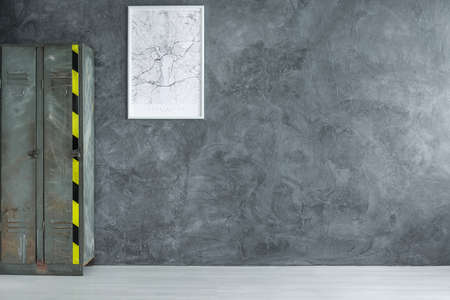 White map in frame on dark concrete wall in empty room with industrial shelf, copy space interior concept  Stock Photo