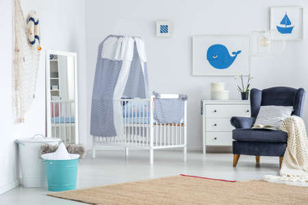 White mirror placed in the corner of baby's room with carpet and decorations Stockfoto