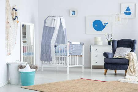 Witte spiegel geplaatst in de hoek van de babykamer met tapijt en decoraties