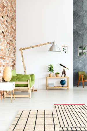 Decorative globe standing on wooden table in bright interior of industrial living room with brick wall, sofa and lamp