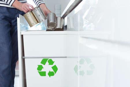 Close-up van vrouw die metaalblikken zetten in container met groen symbool terwijl het sorteren van afval in de keuken Stockfoto