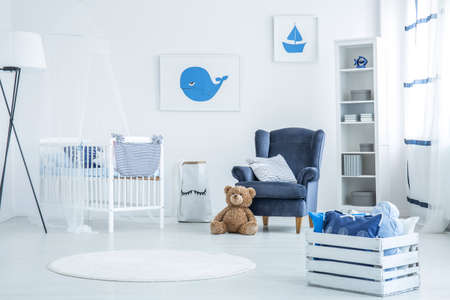 White pallet chest with decorative cushions in marine bedroom for newborn