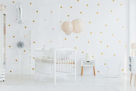 Round boxes placed on white cupboard standing next to rocking horse in newborn baby room with lanterns above crib