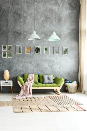 Pastel lamps above comfortable green sofa in cozy eclectic home with earthy interior design and framed leaves on wall