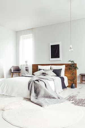 White rug and king size bed with grey bedding in spacious bright bedroom with dark poster