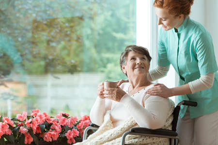 Young doctor in blue uniform standing by the wheelchair of a sick elder woman with cup of tea
