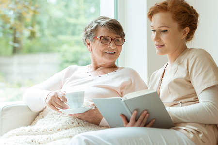 Happy elder woman sitting on white sofa and listening to nurse reading a book out loud