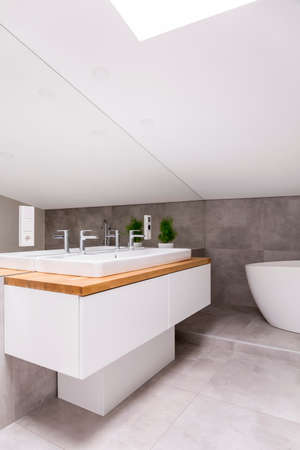 Wooden cupboard with sink and faucet against mirror in classic bathroom in the attic