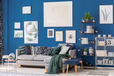 Patterned blanket on corner sofa in living room with stool, tables and posters on blue wall