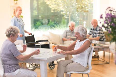 테이블에 앉아서 양로원에서 퍼즐을하는 동안 함께 시간을 즐기고있는 고위 여성