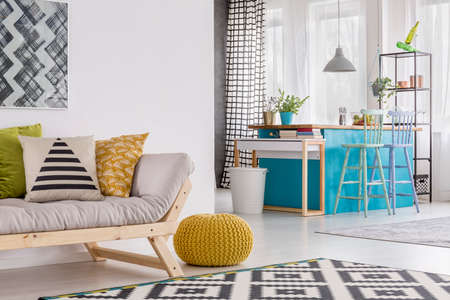 Pillows On Grey Sofa And Yellow Pouf In Spacious Living Room With Stools At  Blue Table