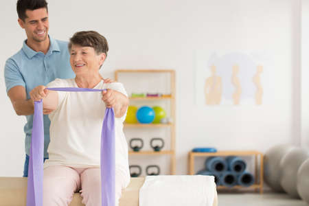 Smiling physiotherapist helping older woman while exercising with resistance band