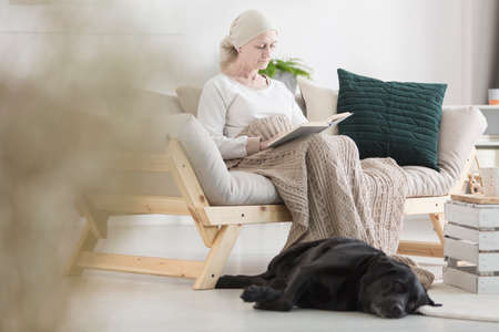 Woman sick with tumor reading a book while her pupil black dog is lying by her side, on the floor