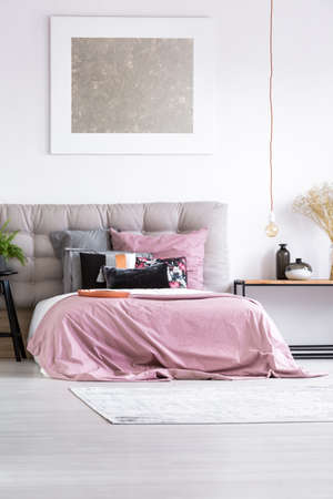 Gray bedhead of king-size bed with pink overlay in contemporary master bedroom with mix of patterned pillows