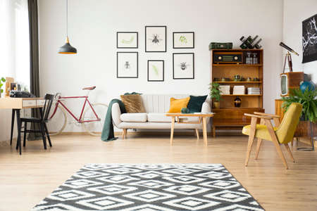Geometric carpet in spacious living room with bike, vintage chair and beige sofa next to wooden sideboard