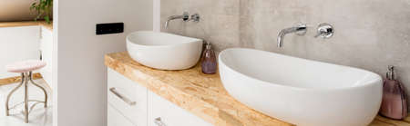 Two washbasins on bright cabinet and stool in classic bathroom interior
