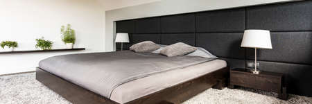 Panoramic shot of a sleeping area with a wooden bed and a headboard covering most of the wall Stock Photo