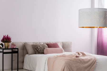 Designer lamp above king-size bed with beige blanket in cozy bedroom with pink plant on nightstand