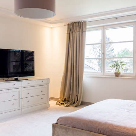 Spacious light bedroom with bed, tv, white commode and big window with decorative curtains