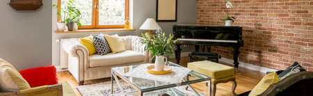 Flowers in vase on glass table in classic living room with white sofa and black piano against brick wall 版權商用圖片