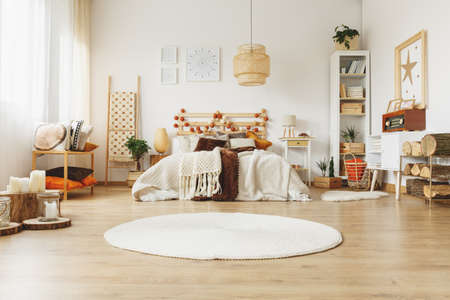 Spacious Scandinavian style bedroom with a king-size bed, circular rug in the middle of a room, and many tree trunks