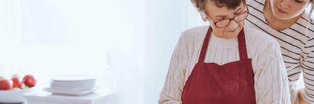 Senior grandmother wearing apron preparing food in the kitchen at home in the company of her adult granddaughter