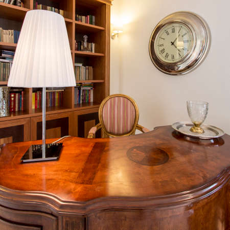 Stylish office with wooden handicraft desk in colonial style, lamp, and upholstered chair